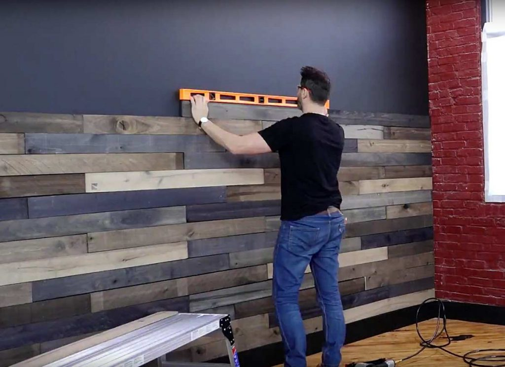 Man leveling wood boards on wall